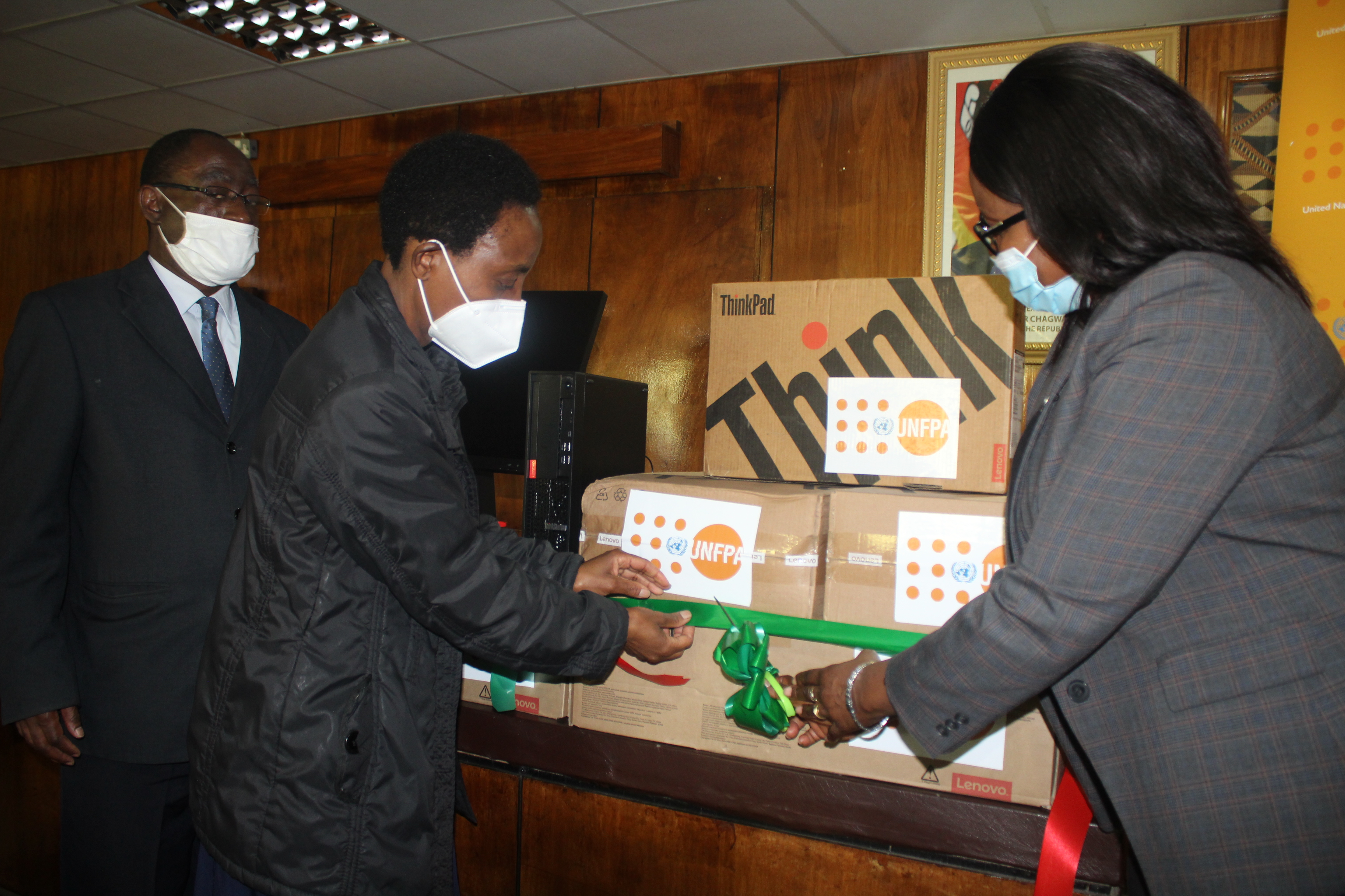 UNFPA Zambia Representative (R) handing over high-tech computer equipment to the University if Zambia Assistant Dean, for use at the Center of Excellence for Geograpic Information System(GIS) and Remote Sensing (RS), as part of ongoing support to enhance the generation and use of geospatial information under the GRID3 project